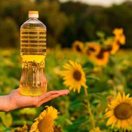 hand-holding-bottle-of-sunflower-oil-with-sunflower-field-in-background